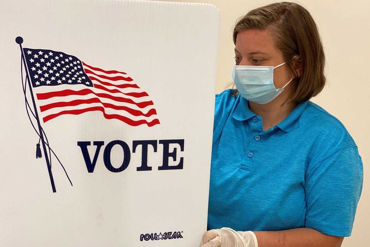 A woman sanitizes a voting station.
