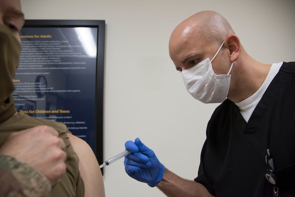 Tech Sgt. Robert Carpenter, 59th Medical Wing Immunizations Clinic licensed vocational nurse, administers the influenza vaccine to a patient.