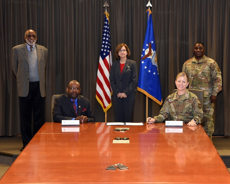 Photo shows five people arranged around a table with the charter placed between them.