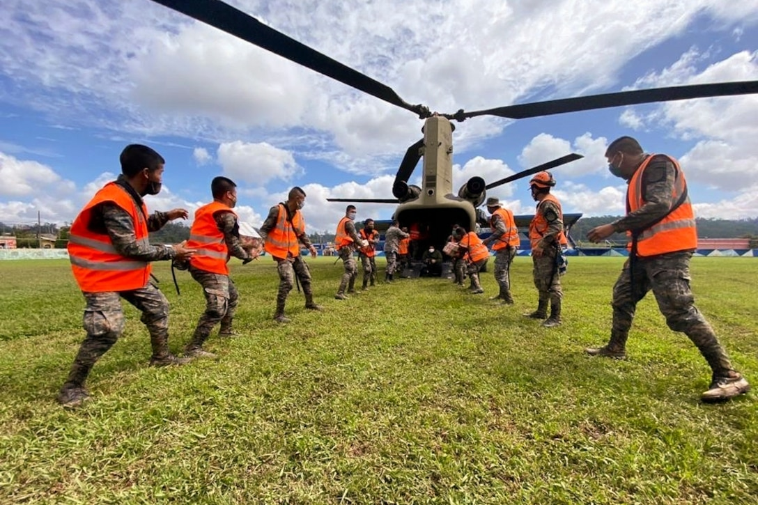 U.S. and Guatemalan troops wearing orange vests unload supplies from a helicopter.