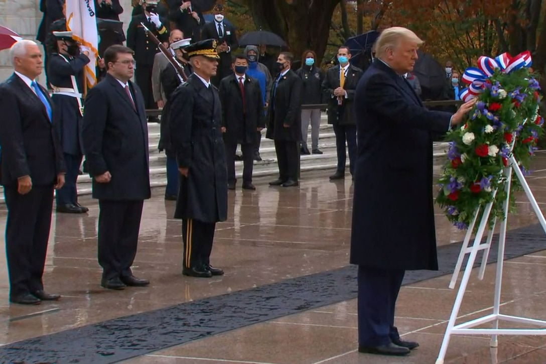 A man touches a wreath. In the background are multiple men and women;  some people wear military uniforms, and others are dressed in suits.