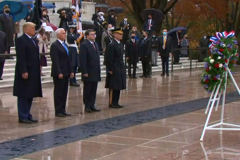 Four men stand in a line and face a wreath. In the background are multiple men and women; some wear military uniforms, and others are dressed in suits.