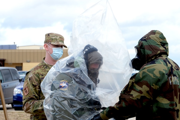 Tech. Sgt. Eric Oestreich, 68th Airlift Squadron loadmaster, wears a plastic cover while being processed for decontamination Nov. 8, 2020, at Joint Base San Antonio-Lackland, Texas. Oestreich, along with other 68th AS and 433rd Operations Support Squadron Airmen, practiced decontamination procedures in order to maintain readiness. (U.S. Air Force photo by Tech. Sgt. Samantha Mathison)