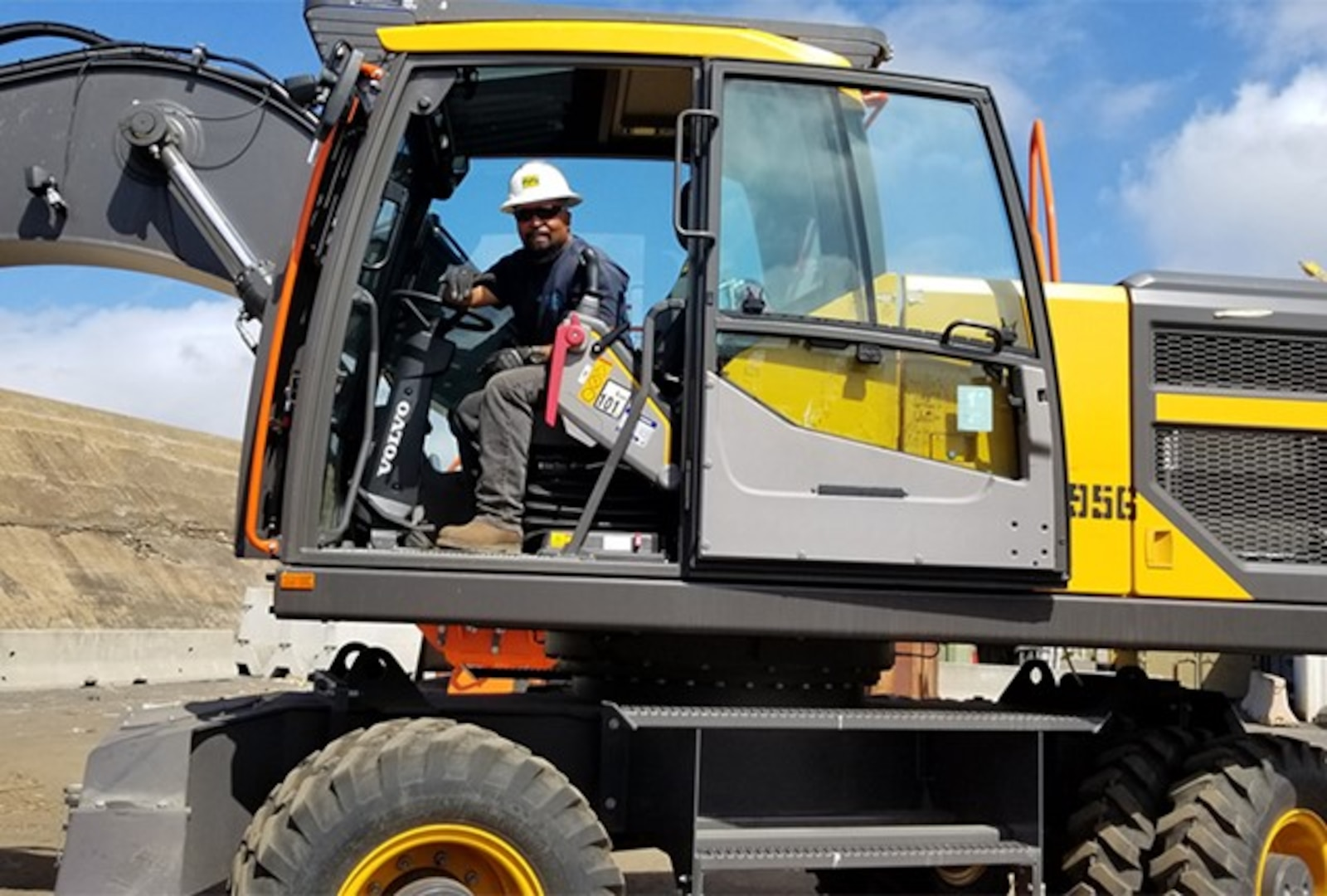 A man with a hard hat sit in the cab of a yellow piece of material handling equipment.