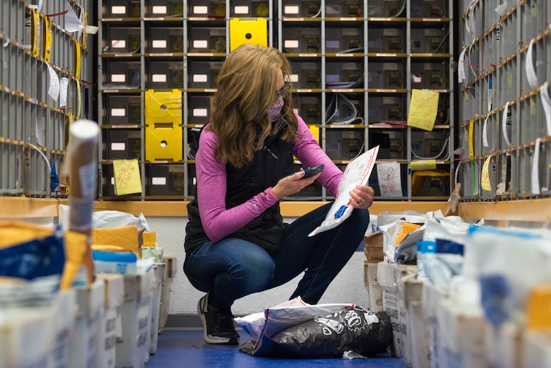 A volunteer scans a package in the Northside Post Office at Ramstein Air Base.