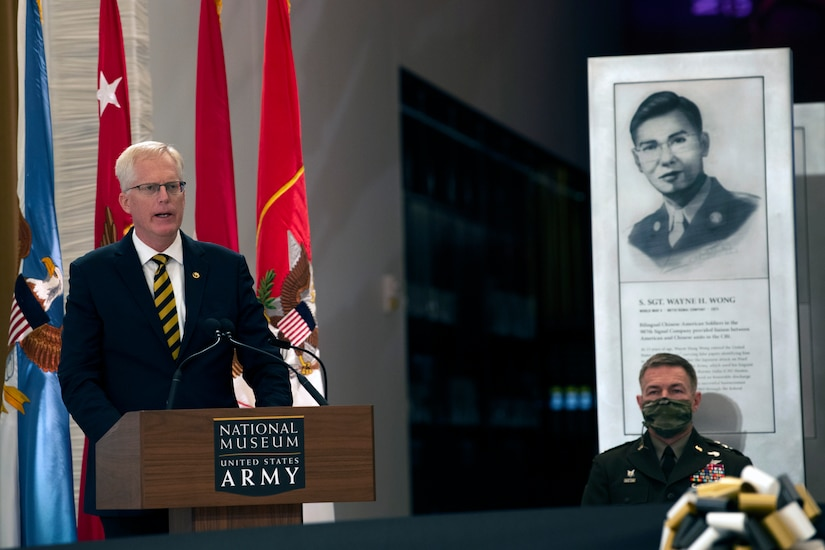 A man speaks from a podium, next to him sits a man in military uniform in front of a historical display.
