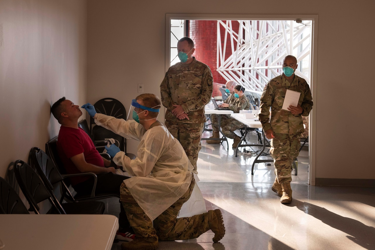 An airman stands by watching another airman administer a nasal swab test to a man.