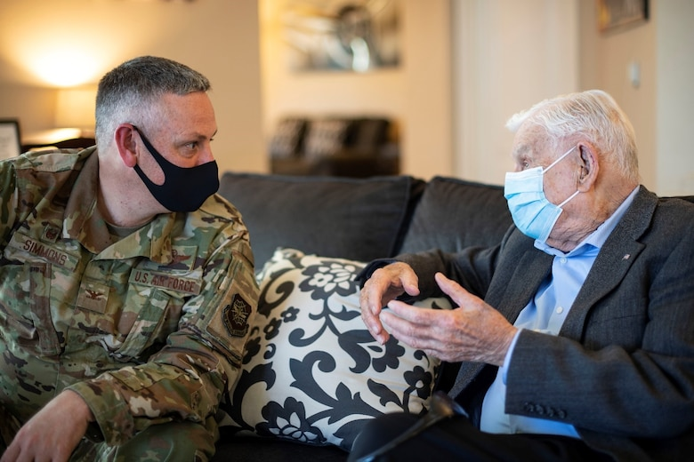 A man in a military uniform speaks to an older gentleman in a suit.