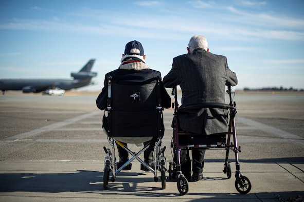 Two men sit next to each other as they look out onto the Travis flight line.