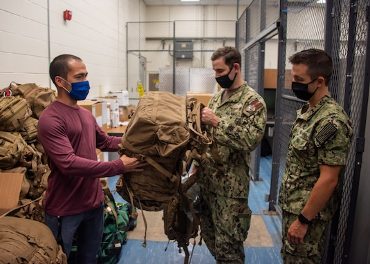 Before the egress testing, Sailors were issued gear to simulate full load out conditions of the Landing Craft Air Cushion. Pictured, Carlos Gonzalez Montanez, issues gear to Hospital Corpsman 1st Class and Hospital Corpsman 3rd Class Kevin Boyaval.