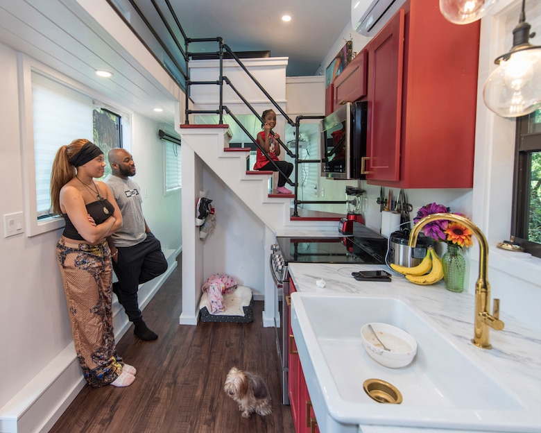 Staff Sgt. Kevin Inniss and his wife, Shanice, along with their dog Quincy, watch as their daughter, Urie, sits proudly on the stairs of the family's newly-constructed Tiny Home.  The Inniss family received a grant courtesy of Operation Tiny Home, a national non-profit organization in partnership with Sutter Home Family Vineyards, to build 400-square-feet of living space to call their own. (U.S. Air Force photo by Matthew S. Jurgens)