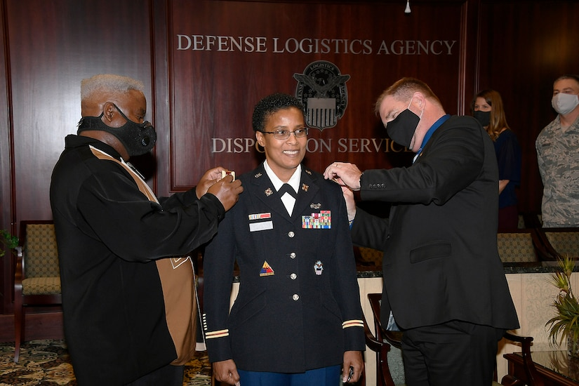 Two men change the rank on female uniform. One her husband, one her director