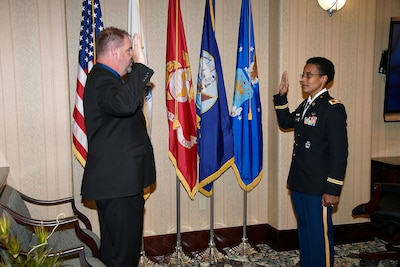 Man in suit and woman in uniform both stand in facing eachother in front of flags with their right hand raised