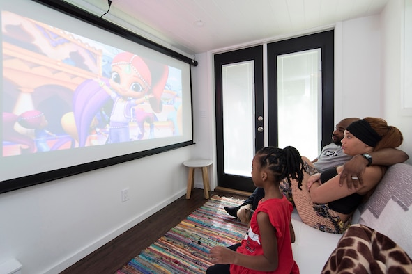 "As their 5-year-old daughter enjoys cartoons on their big screen, her parents, Staff Sgt. Kevin and Shanice Inniss relax on the couch in their 400-square-foot ""Tiny Home.""  Said Inniss, ""As important as it was for us to find a place of our own that we could afford, it was equally important for us to be debt-free while pursuing this goal."" The couple is currently stationed at Patrick AFB, Fla., but has orders to relocate to Germany at the end of the year.  (U.S. Air Force photo by Matthew S. Jurgens)"