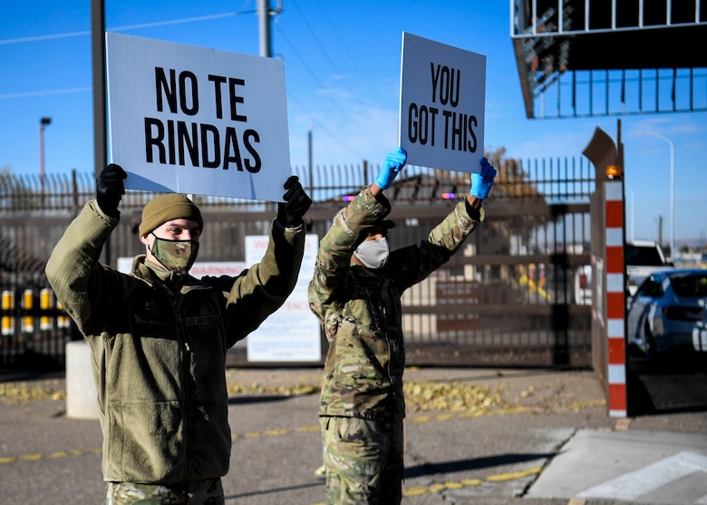 Airmen hold up signs of support.