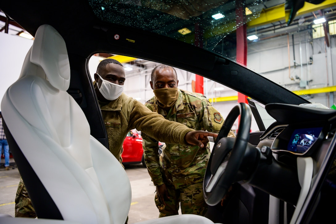 Two airmen look at the driver's side door of a Tesla Model X.