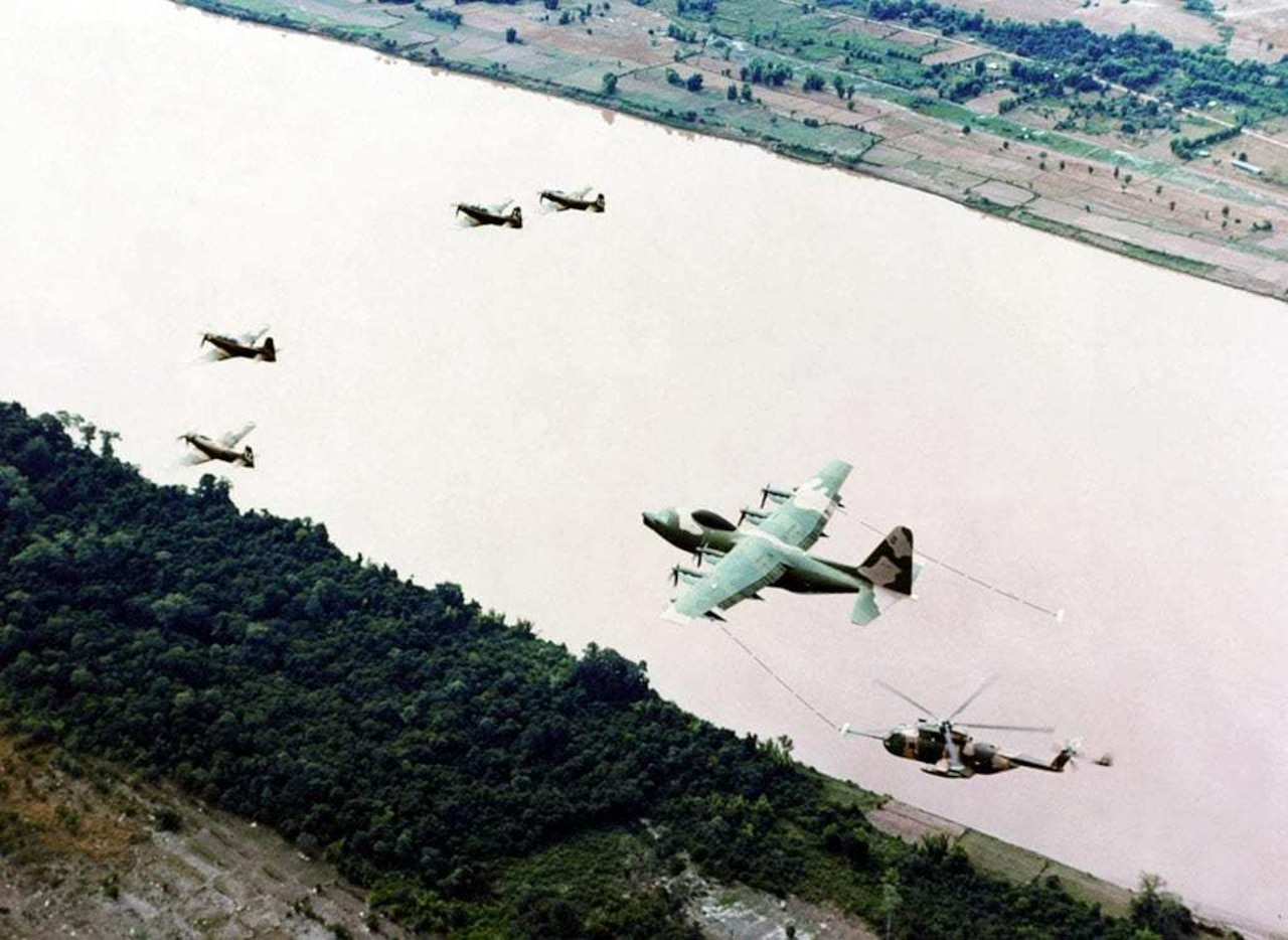 From a birds eye view, multiple aircraft fly along a body of water.