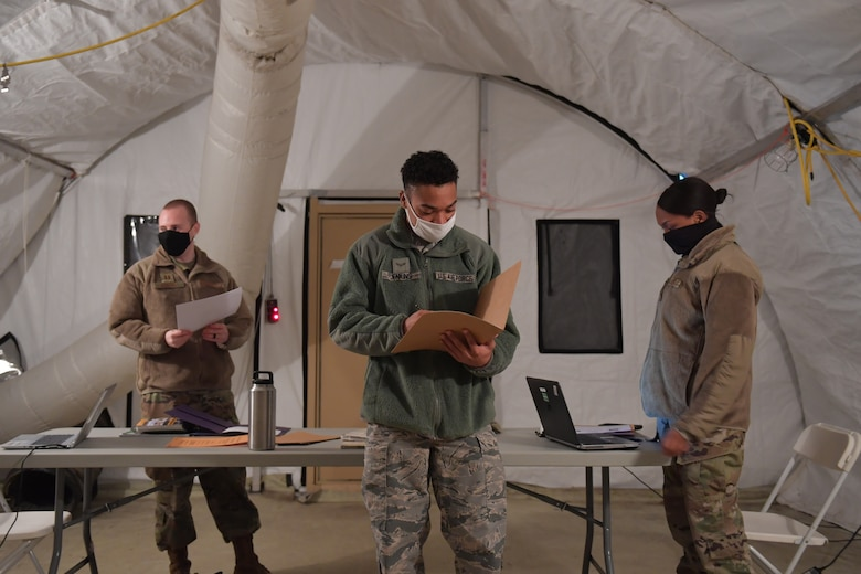 Three Airmen standing in a tent.