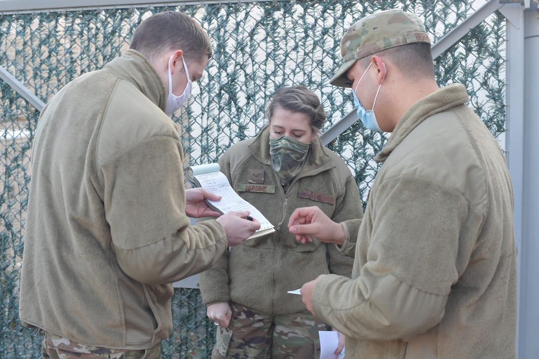 Airmen holding a document to be signed.
