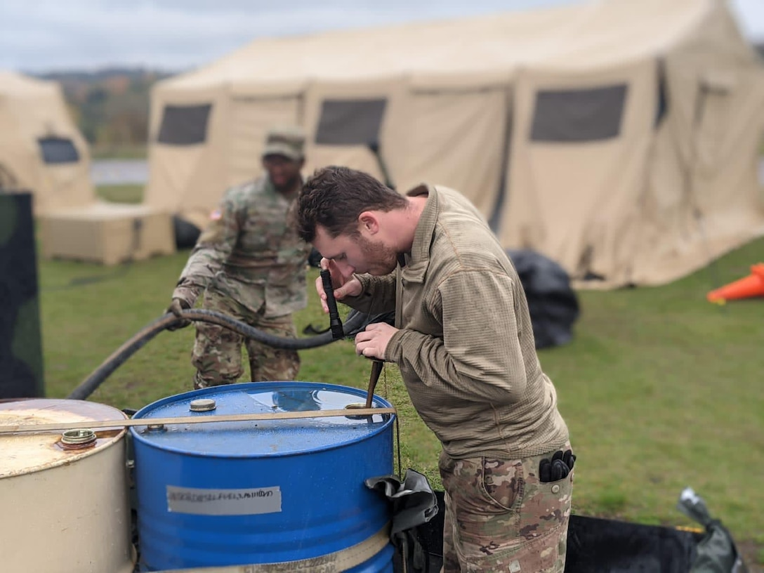 Photo of Airman checking fuel levels in a barrel