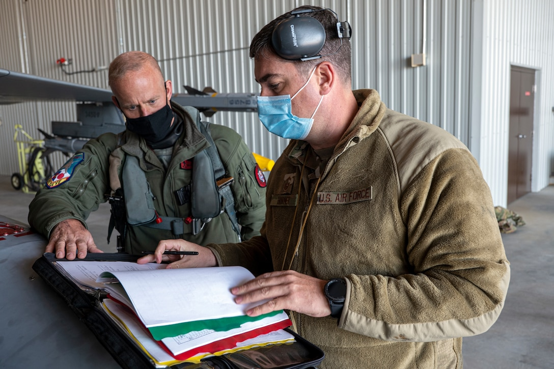 U.S. Air Force Lt. Col. Teneyck Latourrette, a pilot, and Senior Master Sgt. Michael Horner, both from the 140th Wing, Colorado Air National Guard, Buckley Air Force Base, look over aircraft forms before takeoff during Operation Noble Defender, Sept. 21, 2020, 5 Wing Goose Bay, Newfoundland Labrador. North American Aerospace Defense Command conducted a dynamic force employment operation in the Arctic Sept. 20-23 to demonstrate NORAD's air capability, readiness and will to defend the United States and Canada.