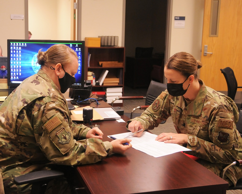 Tech. Sgt. Misty Mayes, 445th Airlift Wing Judge Advocate General office NCO in charge, assists Lt. Col. Jennifer Cowie, 445th Aeromedical Evacuation Squadron operation support flight commander, with an official Power of Attorney for her family care plan.