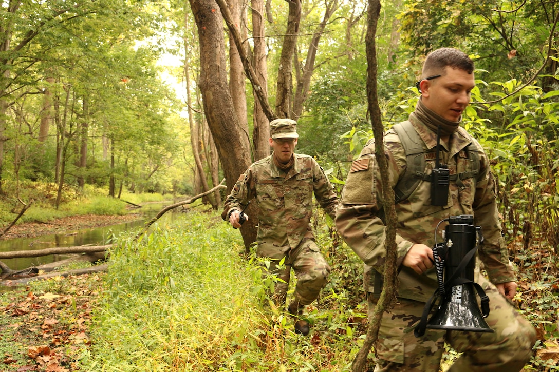Members of the 445th Security Forces Squadron discuss search tactics while participating in combat search and rescue training, Oct. 4, 2020 at Wright-Patterson AFB, Ohio.  The Airmen acted as opposing forces, OPFOR, during the training conducted for Airmen assigned to the 89 Airlift Squadron and the 375th Air Evacuation Training Squadron.