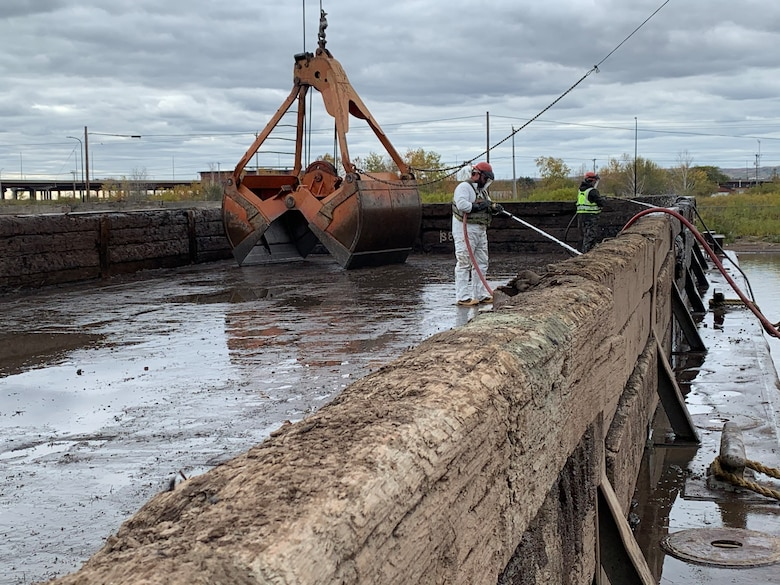 Decontaminating the barge that was used to dewater the contaminated sediments that were dredged out of the AZCON Slip in Duluth, Minnesota before clean material is brought in to construct the cap.