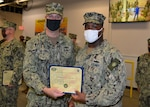 Rear Adm. Eric Ver Hage, Commander, Navy Regional Maintenance Center (left) presents a Navy Afloat Maintenance Training Strategy (NAMTS) Navy Enlisted Classification (NEC) Certificate to EM2 Marcus J. Dexter at Southeast Regional Maintenance Center (SERMC). Dexter earned his NAMTS NEC in
