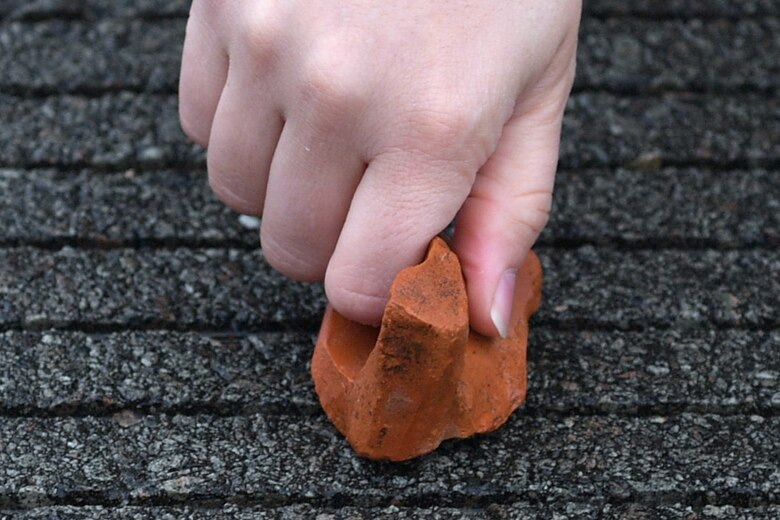 Close-up of a hand picking up a rock.
