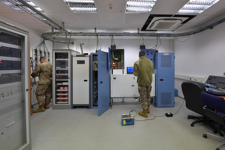Two Airmen standing in a training room.