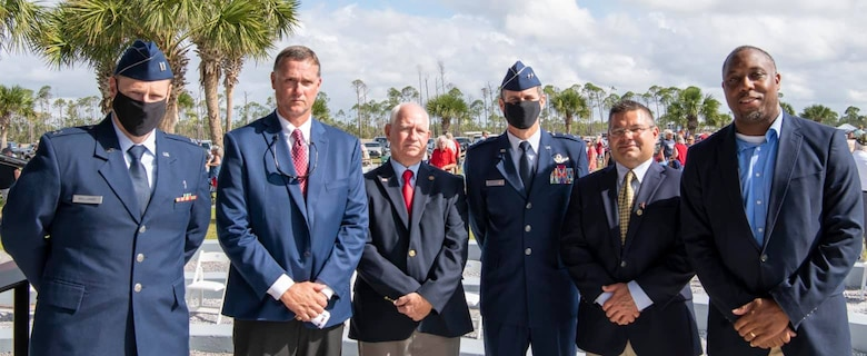 Chaplain (Capt) Jacob Williams (L) and Maj. Gen. Brian Simpler pose with local officials at a ceremony for the unveiling of an Honor Walk for Veterans at Veterans Memorial Park at Beacon Hill, Port St. Joe, Fla.