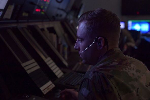 Airmen sitting at workstations with radar screens.
