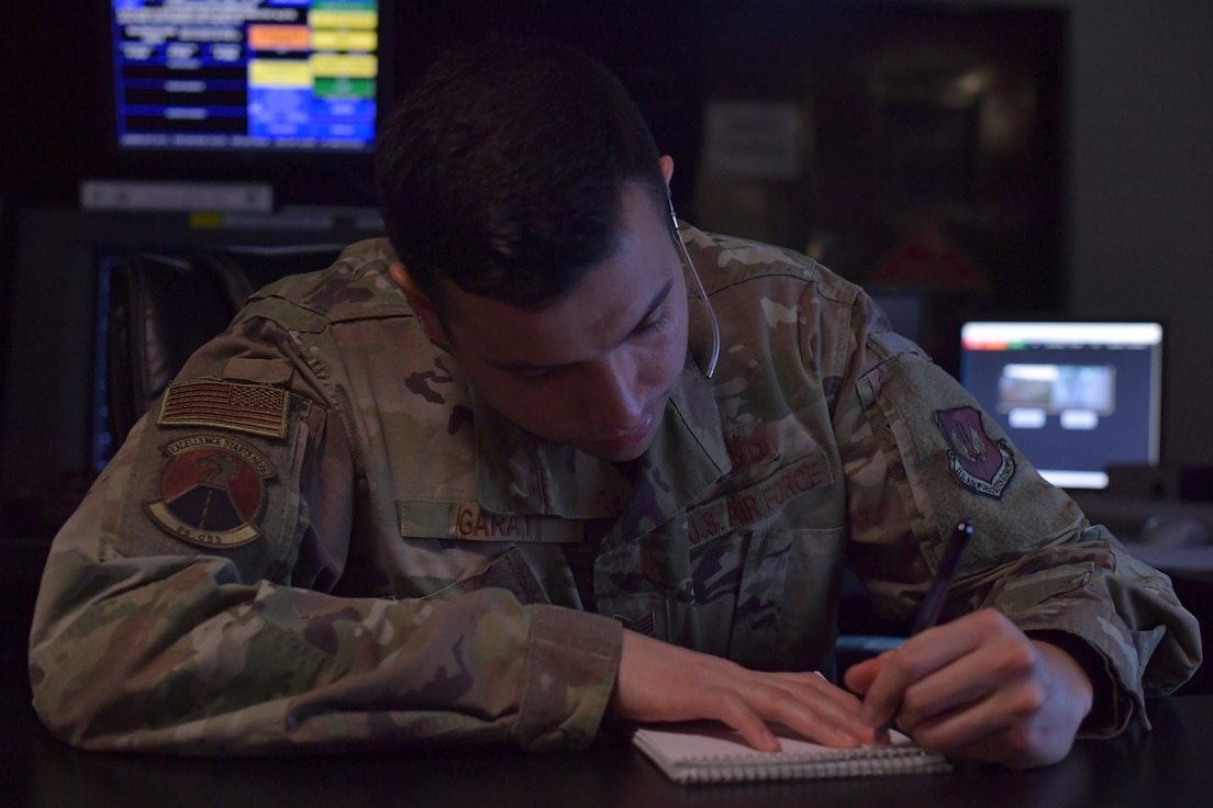 An Airman writing on a notepad.