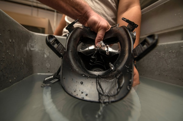 Personnel assigned to the 502nd Logistics Readiness Squadron  utilize a water pump to squeeze water through a gas mask drinking tube to clean out a gas mask more efficiently Nov. 13 at Joint Base San Antonio-Lackland.