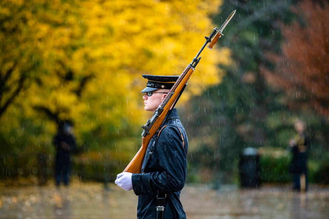 A soldier walks in the rain holding a rifle.
