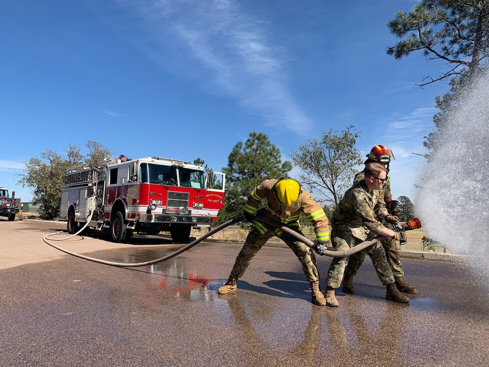 Security Forces and Fire Airmen Practice using a fire hose to put out a fire.