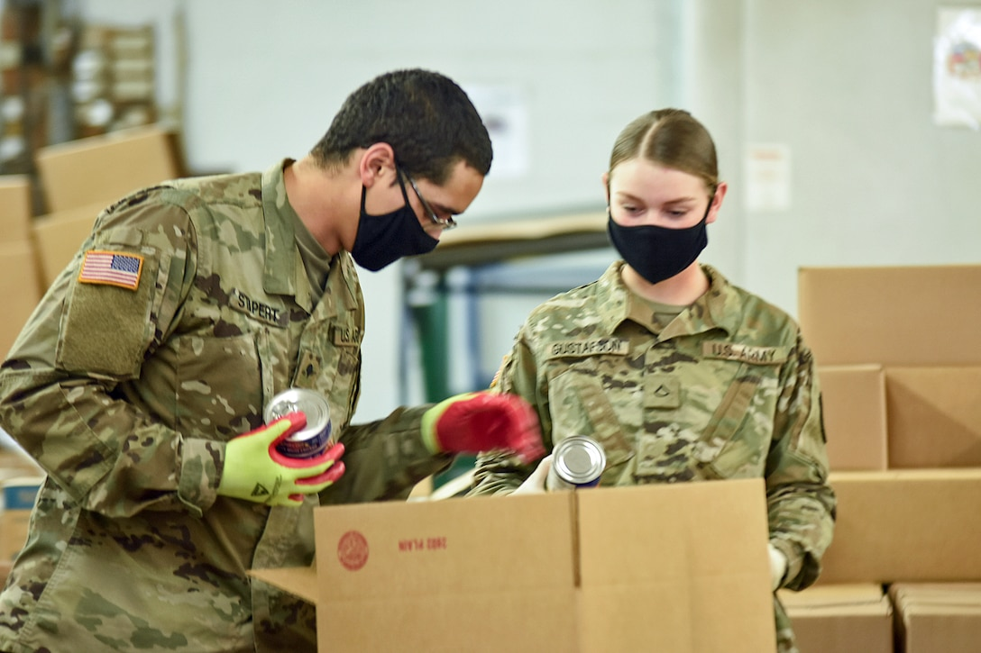 Two National Guard soldiers in black face masks put cans in a cardboard box.