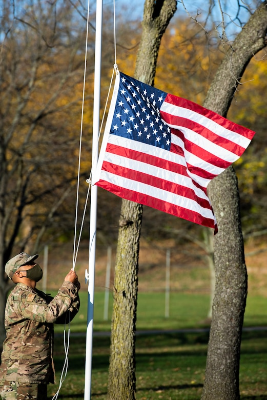 An Airman from Wright-Patterson Air Force Base, Ohio, raises the American Flag at the start of the Veterans Day Ceremony, in Huber Heights, Ohio, Nov. 11, 2020. Members of Wright-Patt also provided they keynote address and performed the raising of the colors.