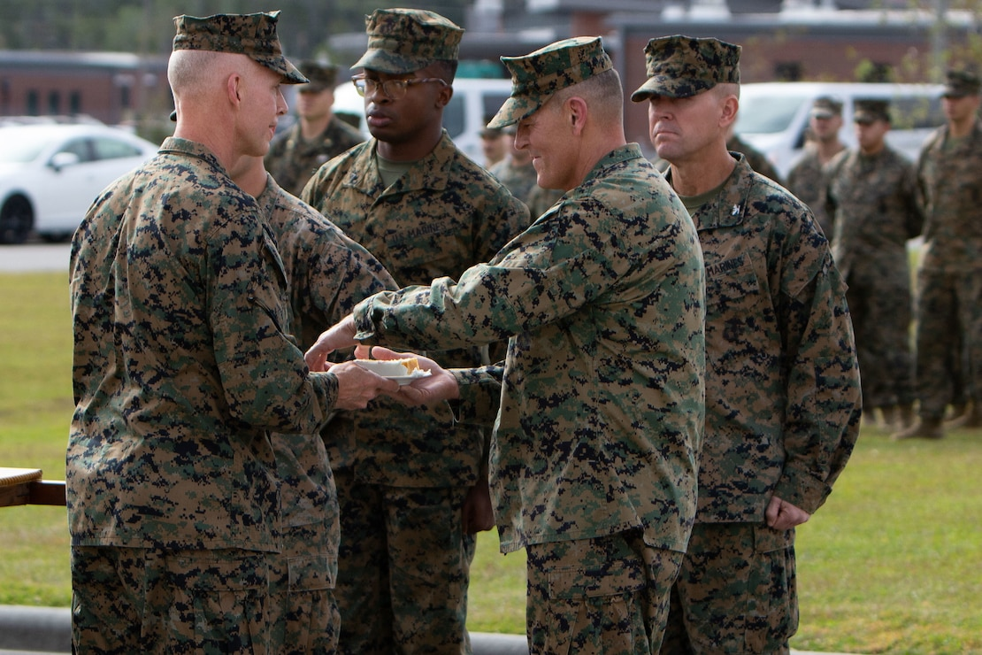 Maj. Gen. James F. Glynn, commander of Marine Forces, Special Operations Command, passes a piece of the cake to the guest of honor, Lt. Gen. George W. Smith, Deputy Commandant for Plans, Policies and Operations, during the 245th Marine Corps Birthday cake cutting ceremony at Camp Lejeune, North Carolina, Nov. 6, 2020. Marine Raiders also ran a collective 245 miles. COVID-19 restrictions have changed the way Marines across the globe are celebrating the Corps' 245th birthday. The annual galas, held to commemorate the founding of Marine Corps, have been scaled back to ensure the health of the force while ensuring the most meaningful aspects of the festivities remain untouched.  (U.S. Marine Corps photo by Cpl. Jesula Jeanlouis)