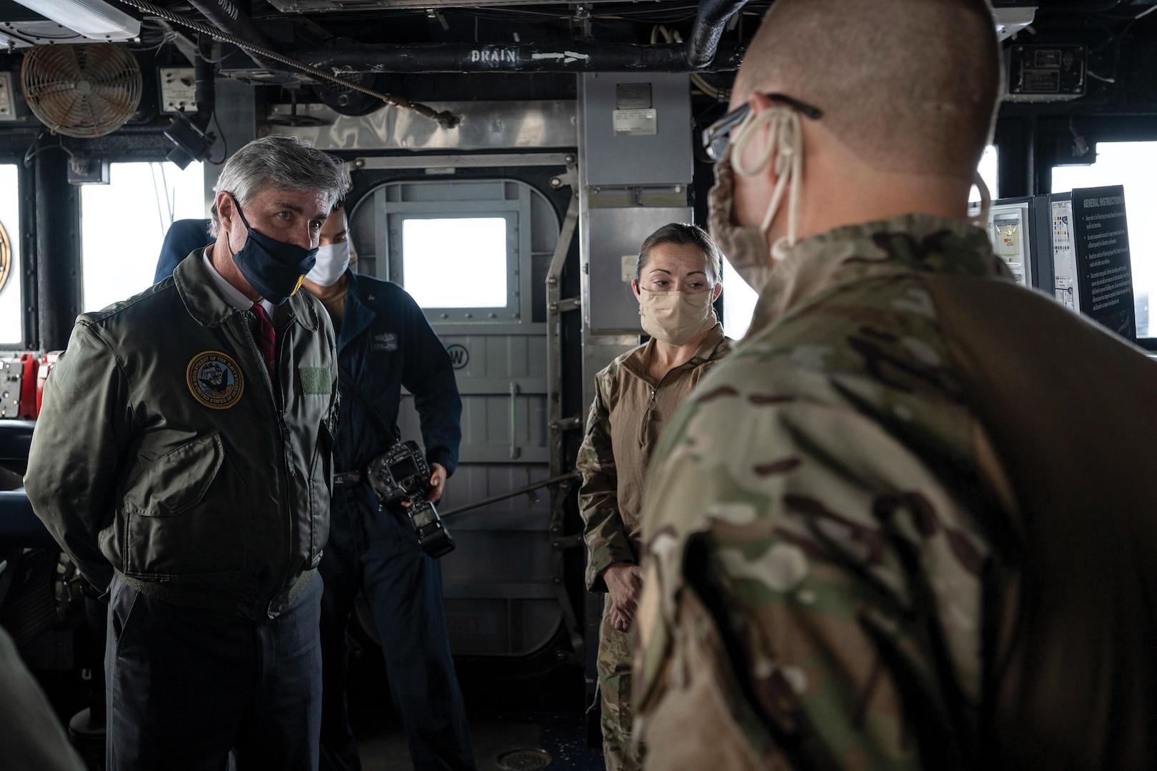 Members of USS Normandy visit, board, search, and seizure team brief Navy Secretary Kenneth Braithwaite