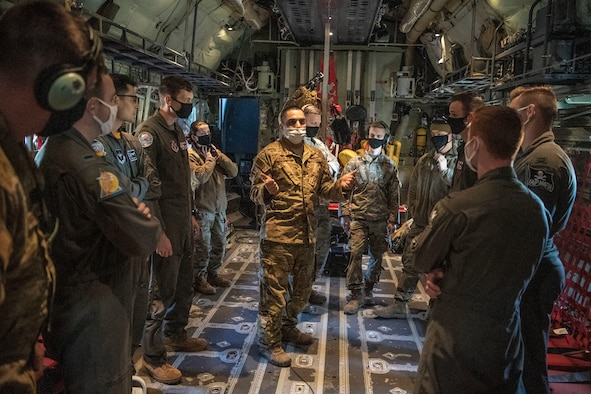 A loadmaster speaks with student pilots before a flight.