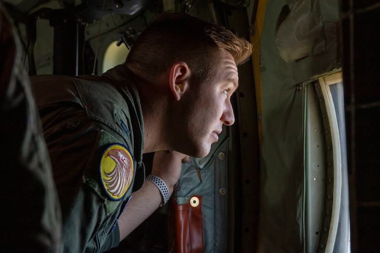 A student pilot looks out the side window of a C-130J.