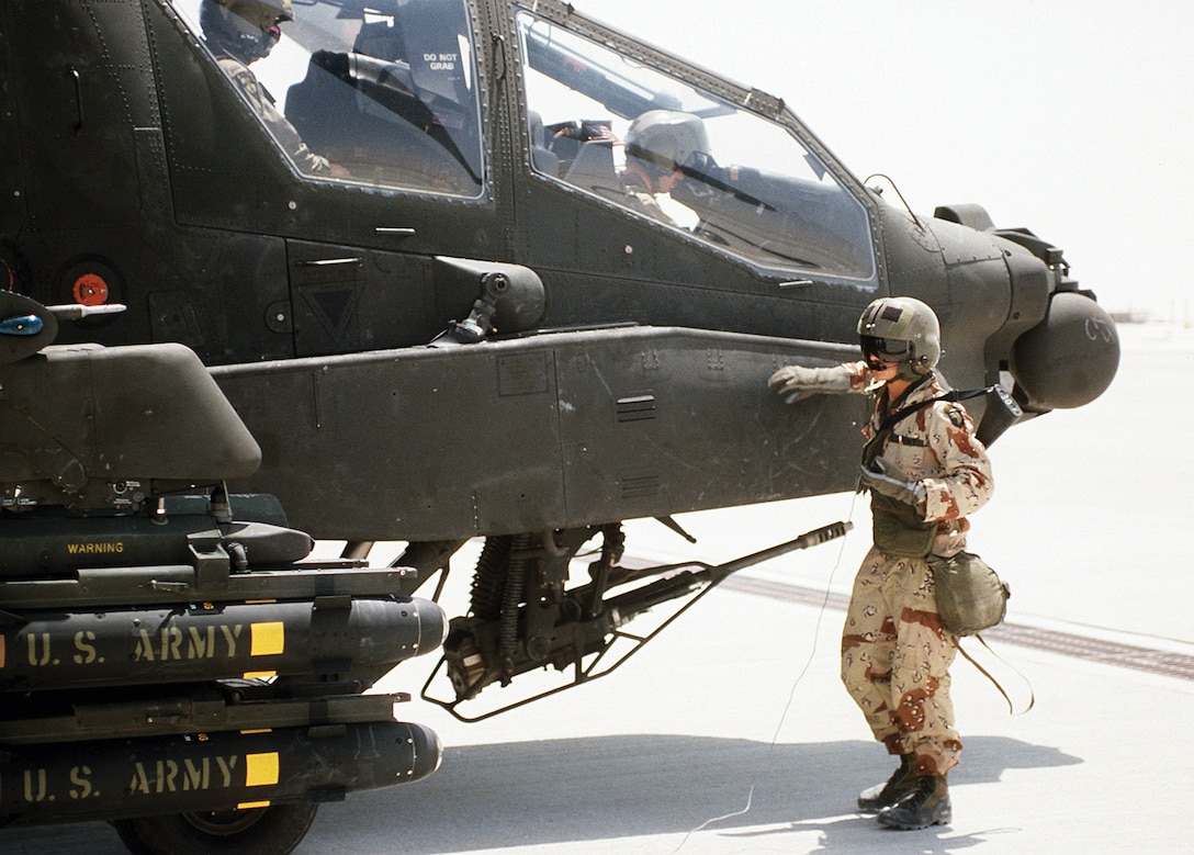 Crewman from 101st Airborne Division (Air Assault) stands beside AH-64A Apache helicopter