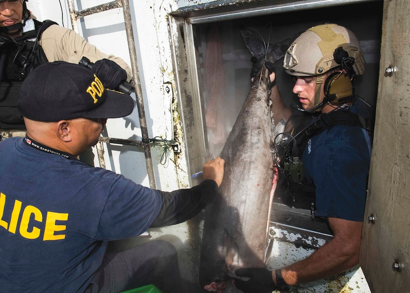 Palauan law enforcement official and Sailor assigned to USS Spruance inspect foreign fishing vessel