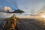 Sailors signal to MH-60S Sea Hawk helicopter as it hovers over flight deck of USS McCampbell