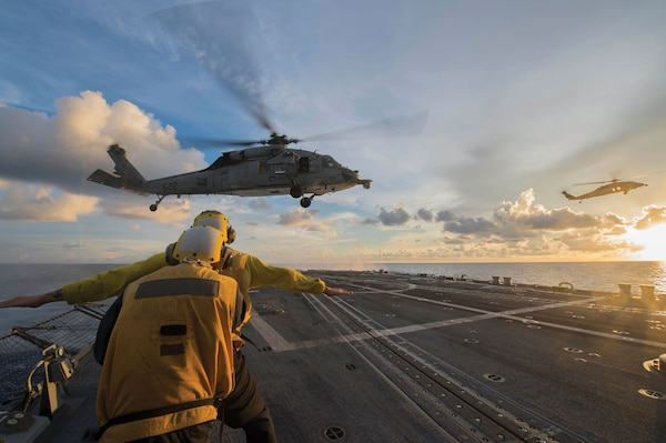 Sailors signal to MH-60S Sea Hawk helicopter attached to Golden Falcons of Helicopter Sea Combat Squadron 12 as it hovers over flight deck of USS McCampbell during visit, board, search, and seizure training exercise, South China Sea, July 22, 2016 (U.S. Navy/Elesia K. Patten)