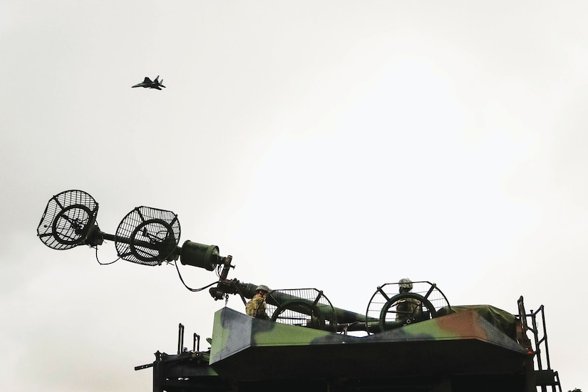 Air Force fighter jet flies overhead as two Soldiers raise signal tower for Patriot missile system