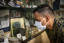 U.S. Navy Petty Officer 3rd Class Roberto Solis, a hospital corpsman with Marine Medium Tiltrotor Squadron 165, Marine Aircraft Group 16, 3rd Marine Aircraft Wing, looks at historical artifacts inside the museum at Field Medical Training Battalion - West on Marine Corps Base Camp Pendleton, California, Sept. 23, 2020. This year, FMTB-West is celebrating its 70th anniversary. In the last 70 years, FMTB-West has trained tens of thousands of corpsmen and medical officers for service with the Fleet Marine Force. (U.S. Marine Corps photo by Lance Cpl. Drake Nickels)