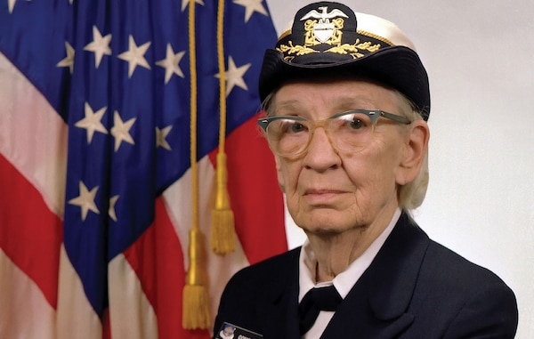 Commodore Grace M. Hopper, USN (covered), popularized idea of machine-independent programming languages that led to